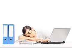 Erschöpfter junger Geschäftsmann, der auf einem Schreibtisch an seinem Arbeitsplatz schläft Stockbild
