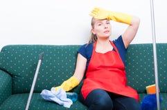 Erschöpfter junger Reiniger, der auf Couch sitzt lizenzfreie stockfotos