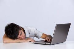 Erschöpfter Mann, der in seinem Büro schläft Lizenzfreie Stockbilder