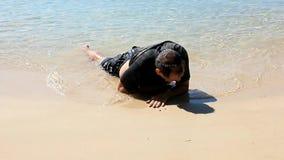 Erschöpfter Mann kroch aus dem Meer heraus stock video