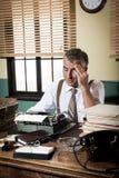 Erschöpfter Retro- Reporter mit Kopfschmerzen lizenzfreies stockfoto