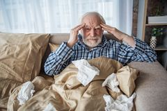 Erschöpftes altes männliches, Kopfschmerzen im Schlafzimmer habend Stockfotografie