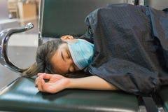 Erschöpftes Mädchen mit der Gazemaske, die auf der Bank liegt lizenzfreie stockfotos