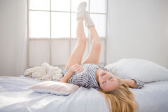Erschöpfte Frau, die mit den Beinen oben angehoben und den geschlossenen Augen liegt Stockfotos