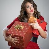 Erschöpfte nette Sankt-Helferfrau überwältigte tragende Weihnachtsgeschenkkästen Lizenzfreie Stockfotografie