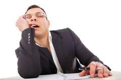 Erschöpfter Geschäftsmann, der an seinem gähnenden Schreibtisch schläft Stockfoto