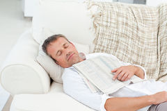 Erschöpfter Mann, der auf der Couch schläft Lizenzfreies Stockfoto