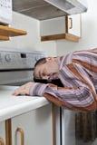 Erschöpfter Mann schlafend in einer Bratpfanne Stockfoto