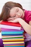Erschöpftes junges Mädchen schlafend auf Buchstapel Stockbild
