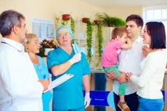 Erschöpftes medizinisches Personal, das gute Nachrichten zu den Verwandten nach langer und schwieriger Chirurgie ankündigt Stockbilder