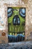 Erschreckende Graffiti des Schädels herein gezeichnet auf den blockierten Eingang Stockfoto
