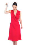 Erschreckender eleganter Brunette im roten Kleid, das Messer hält Stockfoto