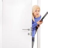 Erschrockene Frau, die ein Gewehr hält und einen Raum betritt Stockfotografie