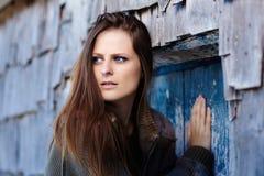 Erschrockene Frau, die in eine Tür drückt Stockbild