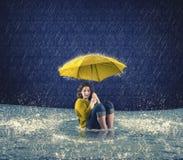 Erschrockene Frau, die einen Regenschirm während es regnend hält Lizenzfreie Stockfotos
