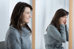 Erschrockene Frau, die gute Laune simuliert Lizenzfreie Stockfotos