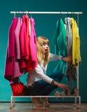 Erschrockene Frau, die unter Kleidung in der Mallgarderobe sich versteckt Lizenzfreie Stockfotos