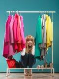 Erschrockene Frau, die unter Kleidung in der Mallgarderobe sich versteckt Lizenzfreies Stockbild