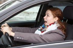 Erschrockene Frau im Auto Stockbild
