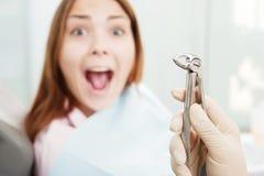 Erschrockene Frau im Büro des Zahnarztes Stockbilder
