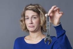 Erschrockene Frau 20s, die Schlüssel für Mechaniker DIY hält Lizenzfreie Stockfotos