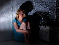 Erschrockene junge Frau mit der ausgestorbenen Lampe, die im dunklen Platz sitzt Stockfotografie