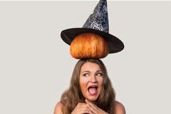 Erschrockene junge Frau mit Halloween-Kürbis und Hexenhut auf ihr er Stockbild