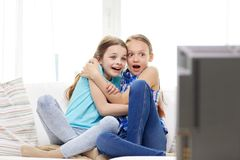 Erschrockene kleine Mädchen, die zu Hause Horror im Fernsehen aufpassen stockfoto