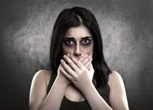 Erschrockene kranke Frau mit den Händen auf Mund Drogenabhängigkeit oder Domest Stockbild