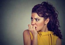Erschrockene nervöse Frau, die ihre Fingernägel besorgt beißt lizenzfreies stockfoto