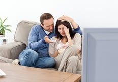 Erschrockene Paare, die einen Horrorfilm überwachen Lizenzfreies Stockbild