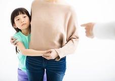 Erschrockene Tochter, die hinter Mutter sich versteckt Lizenzfreie Stockbilder