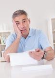 Erschrockener alter Mann, der einen Brief liest Stockbilder