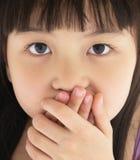 Erschrockener Bedeckungsmund des kleinen Mädchens mit der Hand Lizenzfreie Stockfotografie