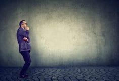 Erschrockener Geschäftsmann auf grauem Hintergrund lizenzfreie stockbilder