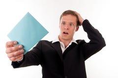 Erschrockener Geschäftsmann mit einem blauen Zeichen in seiner Hand Lizenzfreie Stockfotos