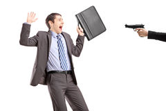 Erschrockener Geschäftsmann von einer Hand, die ein Gewehr hält Stockfotografie