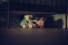 Erschrockener Junge, der unter seinem Bett mit Teddy Bear schläft Stockfoto