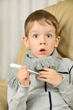 Erschrockener Junge mit einem Thermometer in seinen Händen, die erstaunt schauen Stockbild