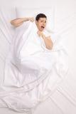 Erschrockener junger Mann, der in Bett legt Stockfoto