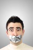 Erschrockener junger Mann, der graues Kanalband auf Mund hat Lizenzfreie Stockbilder