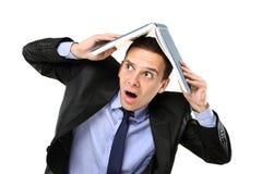 Erschrockener junger Mann, der seinen Kopf mit einem Buch umfaßt Stockfoto