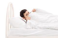 Erschrockener junger Mann, der unter einer Decke sich versteckt Stockbilder