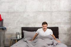 Erschrockener junger Mann wachte von einem Albtraum auf, der in stilvollem sitzt Lizenzfreie Stockbilder