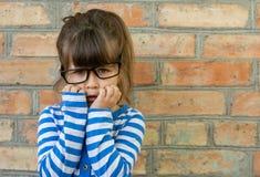 Erschrockener Kinderkleiner Junge im weißen T-Shirt drückt Freude an einer leeren leeren Backsteinmauer aus lizenzfreie stockfotos