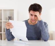 Erschrockener Mann, der ein Dokument liest Stockbild