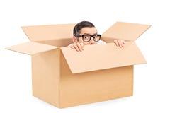 Erschrockener Mann, der in einem Kartonkasten sich versteckt Stockfotografie