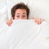 Erschrockener Mann, der im Bett sich versteckt Stockfoto