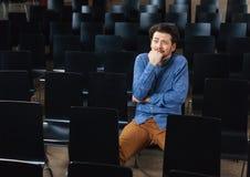 Erschrockener Mann, der im Konferenzsaal sitzt Stockfotografie