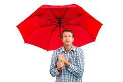 Erschrockener Mann, der oben beim Halten des roten Regenschirmes schaut Stockbild